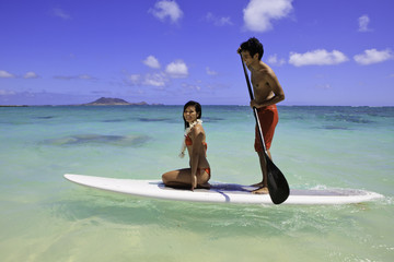 young couple with their paddle board in hawaii