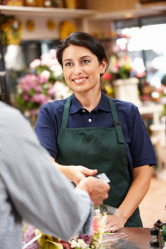 Woman serving customer in florist