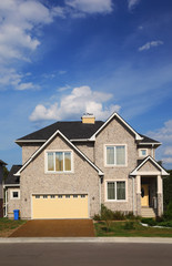 New two-storied beige stone cottage with yellow garage