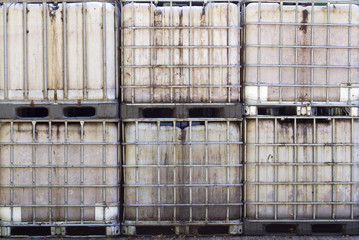 Row of empty old IBC containers