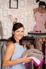 lächelnde verkäuferin mit kleidung