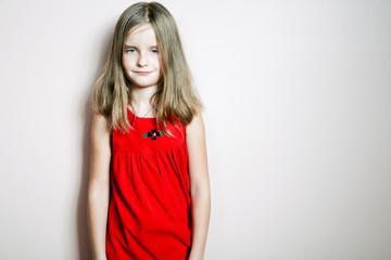 Little happy girl posing in a red dress.