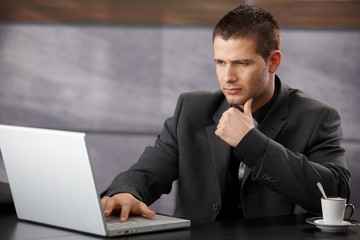 Young businessman using laptop in office