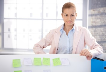 Portrait of young woman standing in office