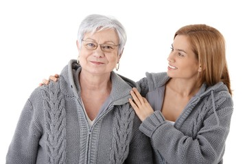 Young woman embracing senior mother smiling