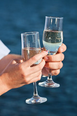 man and woman hands holding champagne glasses