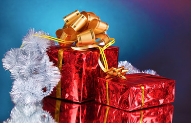 beautiful gifts with gold bows and tinsel on blue background