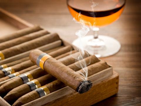 smoking cuban cigar and glass of  liquor on wood
