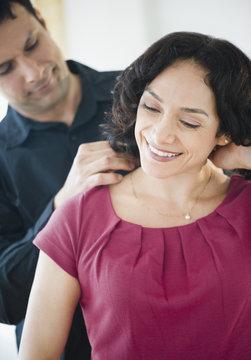 Smiling man giving wife elegant necklace