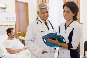 Doctor and nurse discussing patient in hospital room
