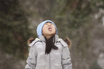 Chinese girl catching snowflakes on her tongue