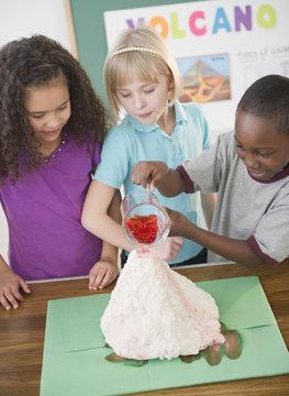 Children watching boy with model volcano