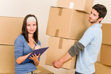 Moving home young couple carrying cardboard boxes
