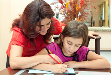 Latin mother helping her daughter with school homework