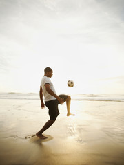 Black man playing with soccer ball on beach