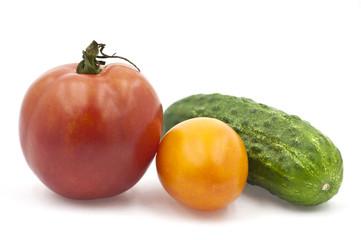 Красный и желтый помидоры рядом с огурцом