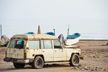 Old rusted 4x4 on a beach in Oman