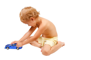 Little cute boy playing with blue toy car