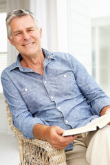 Senior man relaxing at home with a book
