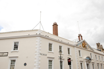 An old white building with Royal Family Coat of Arms
