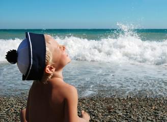 Happy smiling boy sits on seaside