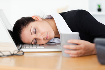 Exhausted businesswoman sleeping at workplace