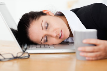Businesswoman sleeping with cup of coffee in her hand