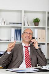 lächelnder geschäftsmann am telefon zeigt daumen hoch
