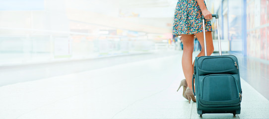 Woman's legs and travel suitcase at modern airport