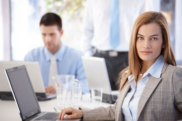 Portrait of pretty businesswoman sitting at desk