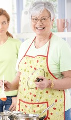 Senior woman cooking smiling happily