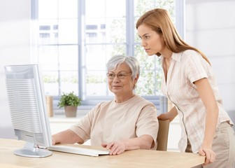 Senior mother and daughter using computer