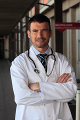 doctor with stethoscope in front of hospital entry