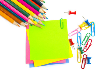 Colored pencils, clips and note paper on white