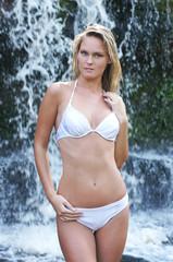 Young and beautiful girl in bikini near the waterfall