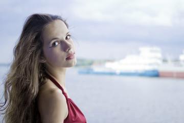 Portrait of beautiful brunette against river landscape