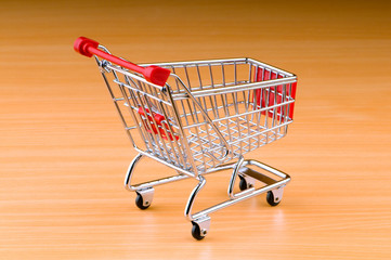 Mini shopping cart against gradient background