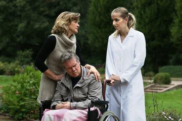 Älteres Paar - Mann im Rollstuhl, mit Pflegekraft