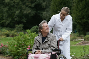 Älterer Herr im Rollstuhl mit Pflegekraft
