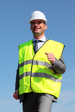 young businessman with hardhat and yellow vest