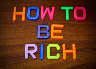 How to be rich in colorful toy letters on wood background