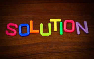 Solution in colorful toy letters on wood background