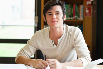 Smiling male student writing an essay