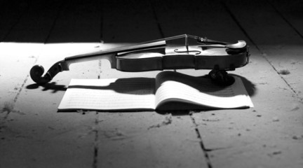 a romantic violin with a musical score in the light in a dusted attic in black and white