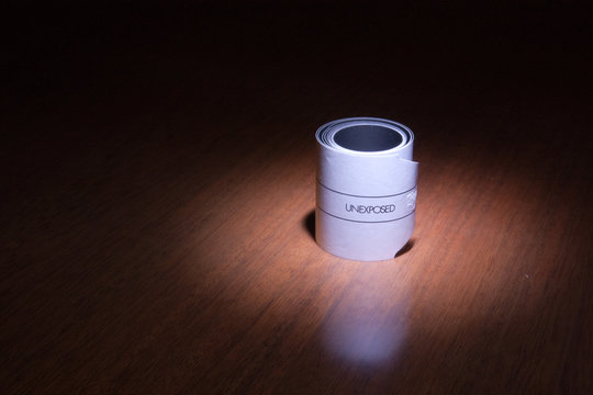 a 120 photographic film unexposed in the light on a wood table