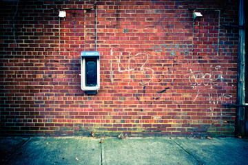 Obsolete Payphone on a Grungy Urban Brick Wall