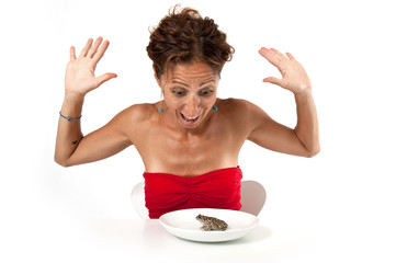 Surprised woman looking at a toad in her plate.