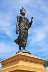 Buddha statue stand in blue sky, Thailand