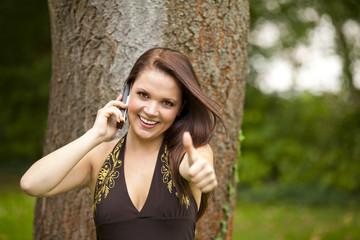 lächelnde junge Frau mit Mobiltelefon zeigt Daumen hoch