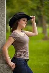 nachdenkliche junge Frau mit Cowboyhut lehnt an Säule